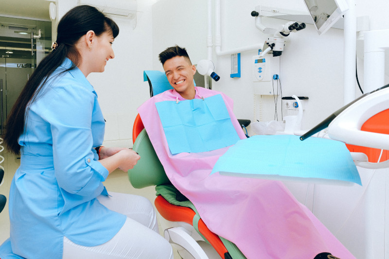 A young man sitting in a dentist's examination chair, smiling, while a dentist sits on a stool next to him, also smiling.