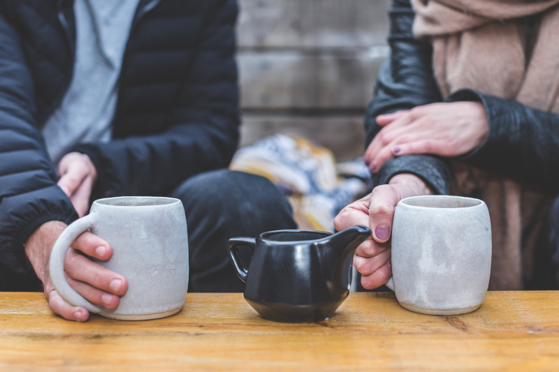 An older couple wearing coats and scarves holding grey mugs on a table, a black ceramic teapot between them.