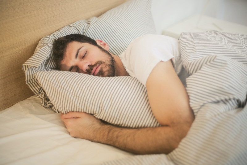 A man sleeping soundly in his bed, striped sheets pulled up around him.