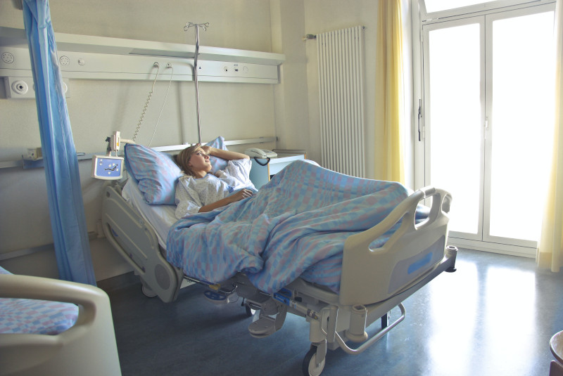 A woman lying in a hospital bed, gazing out the brightly lit window.