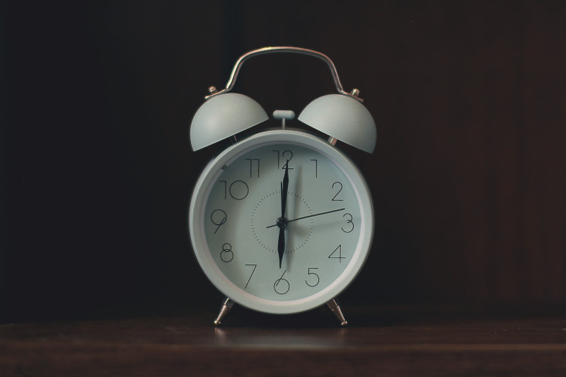 A white, analog alarm clock with two large bells on top sitting on a wooden table.