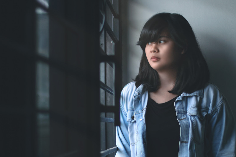 A young woman wearing a denim jacket looks through the window blinds in a shadowy room.
