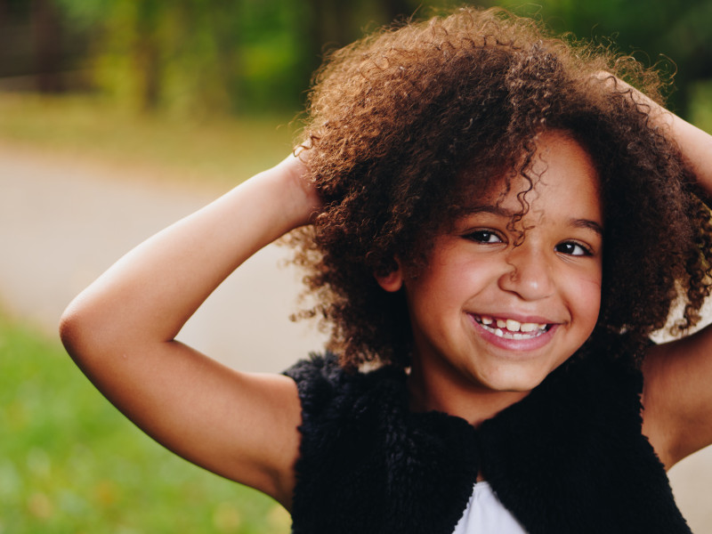 A young girl with long curly hair and a wide, toothy grin