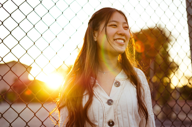 A woman standing against a fence, smiling during a sunset.