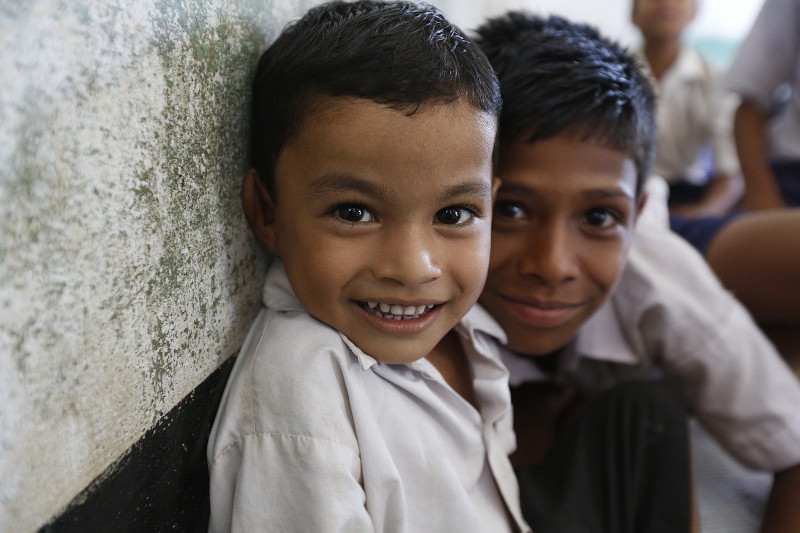 Two young boys smiling at the camera.