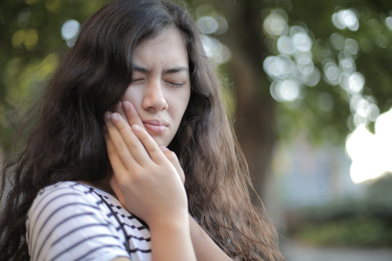 A woman placing both hands on the side of her mouth, with a look of pain on her face.