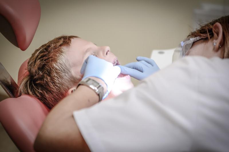 A dentist works on a child's teeth.