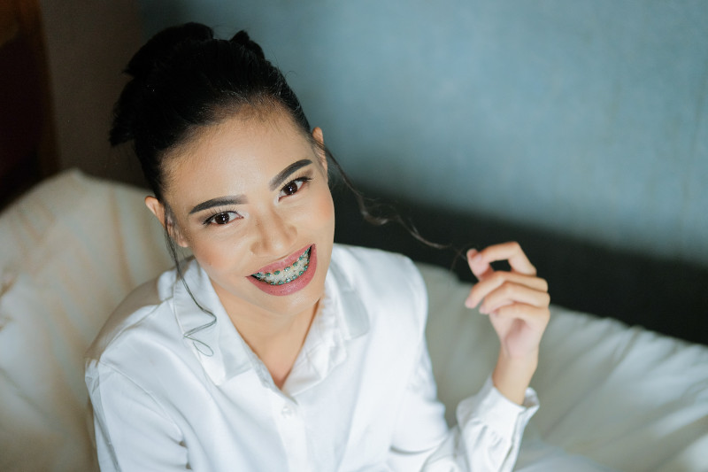 A young woman with braces smiling.