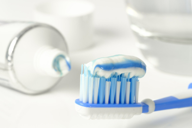 A toothbrush loaded with fluoride toothpaste — a useful tool for stopping the demineralization of teeth — lying next to an open tube of toothpaste.
